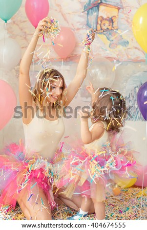 Mother day concept. Happy woman and young girl celebrate birthday plaing confetti.  - stock photo