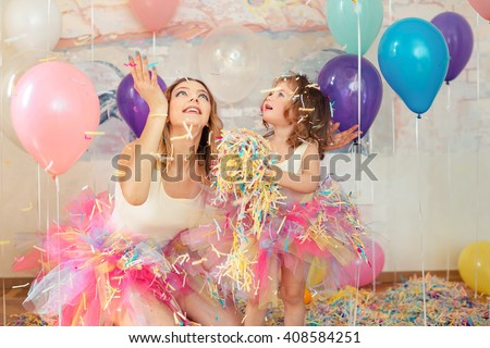 Mother day concept. Happy woman and young girl celebrate birthday playing confetti.  - stock photo
