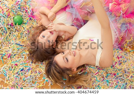 Mother day concept. Happy woman and young girl celebrate birthday playing confetti, lie on a floor and embrace - stock photo