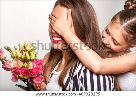 Mother Day.Mother and daughter in the studio gives beautiful flowers, daughter of  mother closes her eyes on a white background  - stock photo