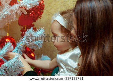 Mother decorates the Christmas tree with her little baby girl. New year. Christmas mood. - stock photo