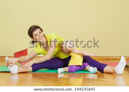 Mother do physical exercises with her daughter at home - stock photo