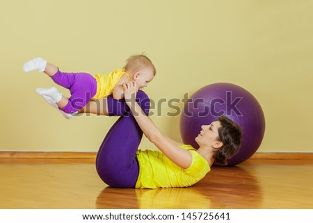 Mother does physical exercises with her daughter at home - stock photo