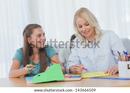 Mother doing arts and crafts with her daughter at home in living room - stock photo