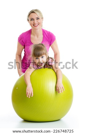 mother doing gymnastics with daughter kid on fitness ball - stock photo