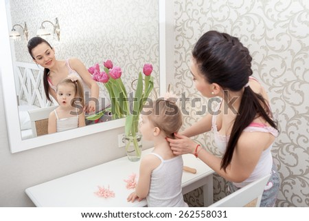 Mother doing her little daughter's hair near mirror - stock photo