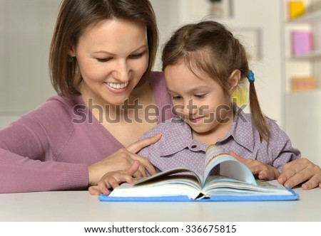 Mother doing homework with her daughter  at home