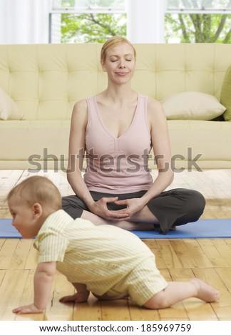 Mother Doing Yoga near Baby Boy - stock photo