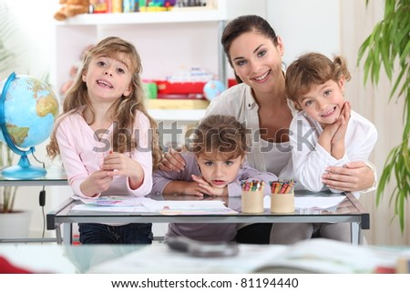 Mother drawing with three daughters - stock photo