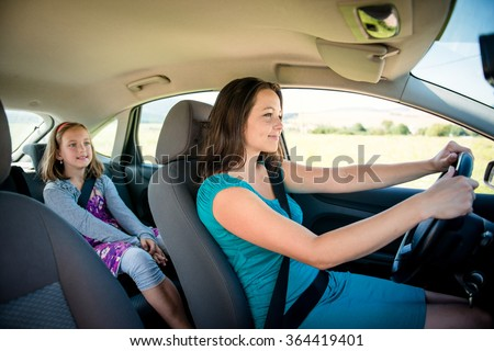 Mother driving car and child sitting on back seat