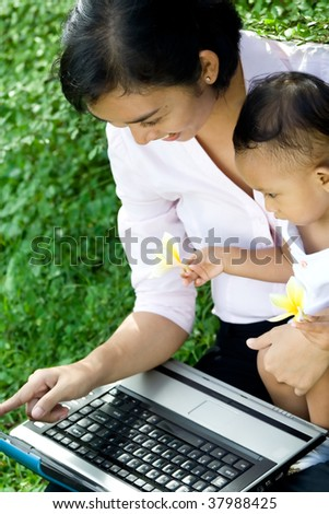 Mother educate her cute baby girl using a laptop - stock photo