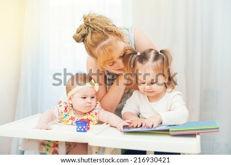 mother educating her baby daughters - stock photo