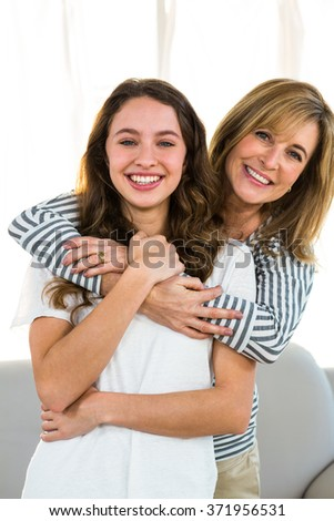 mother embrace her daughter and smiling to the camera - stock photo