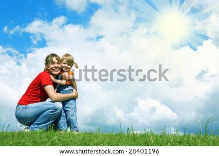 mother embrace little daughter on green grass under blue sky - stock photo