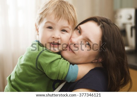 mother embraces the son in the room
