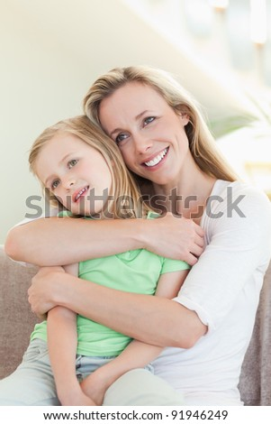 Mother embracing daughter on the sofa