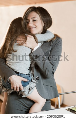 Mother embracing her little girl before leaving to work/or just back from work - stock photo