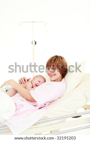 Mother embracing her newborn baby in hospital with copy-space