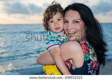 Mother embracing her toddler boy at sunset on beach  - stock photo