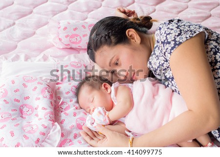Mother embracing sleeping baby, asian family. selective focus. - stock photo