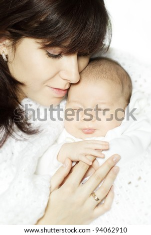 Mother embracing sleeping newborn baby and holding his hand. Child is wrapped in woolen blanket - stock photo