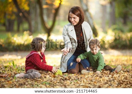 Mother enjoying with her children in autumn park. - stock photo