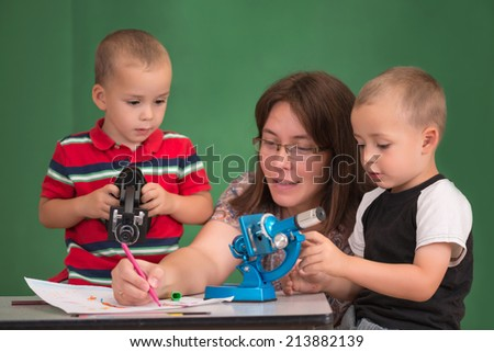 Mother enjoys drawing with her children.Selective focus on one child. - stock photo