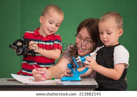 Mother enjoys drawing with her children. Selective focus on one child. - stock photo