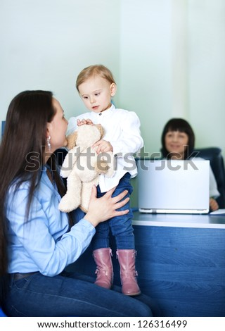 Mother entertaining her daughter at doctors office - stock photo