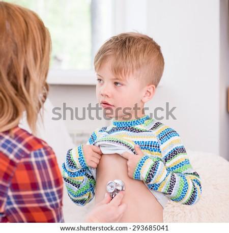 mother examining boy with stethoscope - stock photo