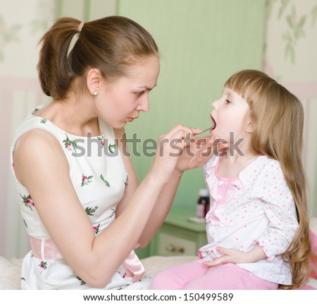 mother examining little girl's throat  - stock photo