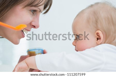 Mother face in front of a baby in living room - stock photo