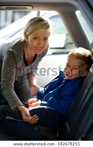 Mother fastening his son's seat belt - stock photo