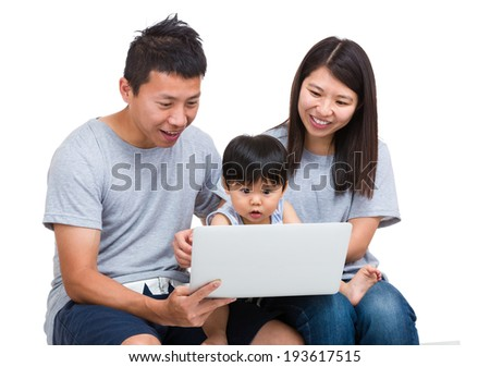 Mother, father and baby son looking at laptop computer - stock photo