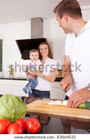 Mother father and child in the kitchen with the father cutting vegetables. - stock photo