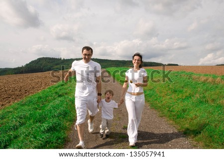 Mother, father and child run down the road.