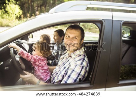 Mother, father and children - son and daughter pretend driving car sitting all on front seats