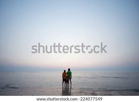 Mother, father and daughter embrace together at ocean beach  on sunset - stock photo
