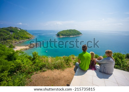 Mother, father and daughter embraces and sit on tropical island cliff with small beach below - stock photo