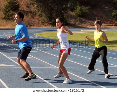 Mother, father and daughter exercising on a blue racetrack - stock photo