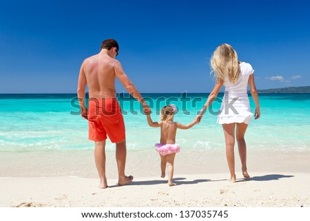 Mother, father and daughter having fun on tropical white beach - stock photo