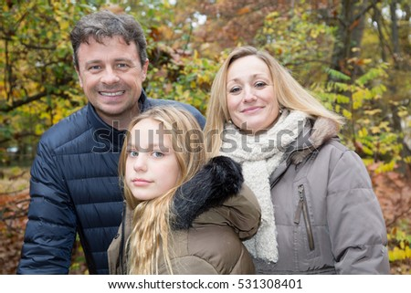 mother father and daughter in an autumn park
