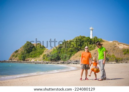 Mother, father and daughter walk along tropical beach holding hands with lighthouse on back - stock photo