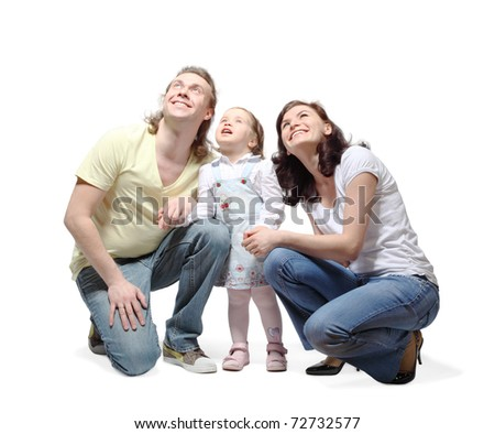 Mother, father and little daughter sit down, hold hands and fixedly looking up with smile - stock photo