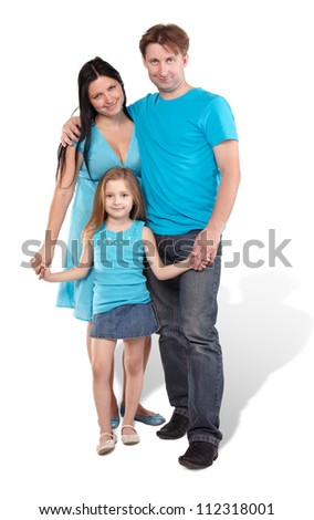 Mother, father and little daughter stand embraced and holding hands - stock photo