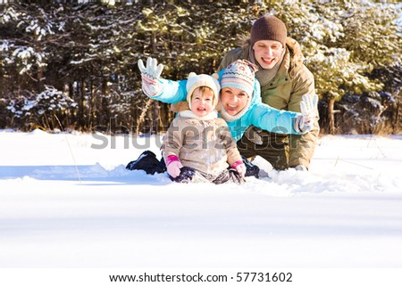 Mother, father and little girl in snow - stock photo