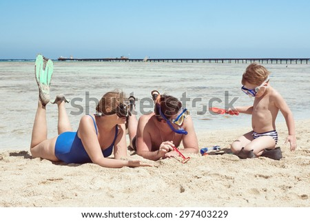 Mother, father and little son on summer vacation at the seaside, They wearing snorkels and flippers while lying and playing on the beach - stock photo