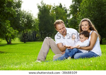 Mother, father and small son have a rest on lawn in summer park - stock photo
