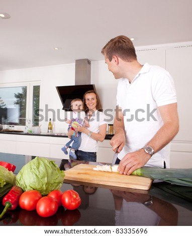 Mother, father and son in kitchen, shallow depth of field with critical focus on father - stock photo