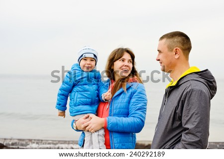 Mother, father and son near the sea - stock photo